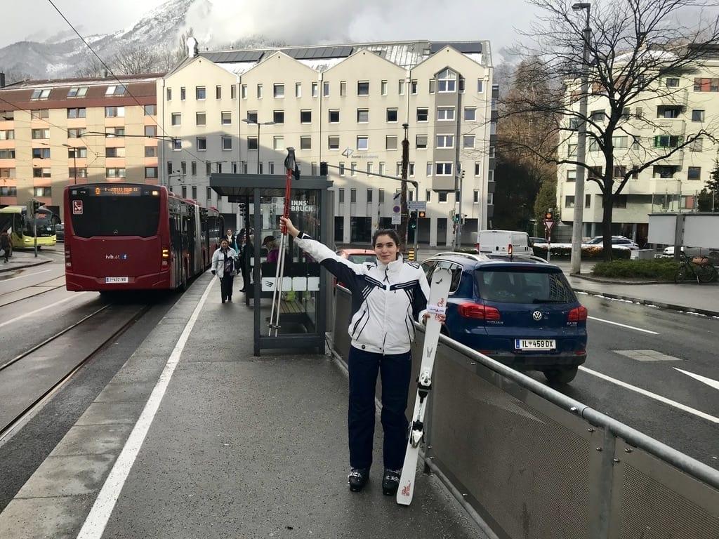Sara steht mit Ski bei der Bushaltestelle