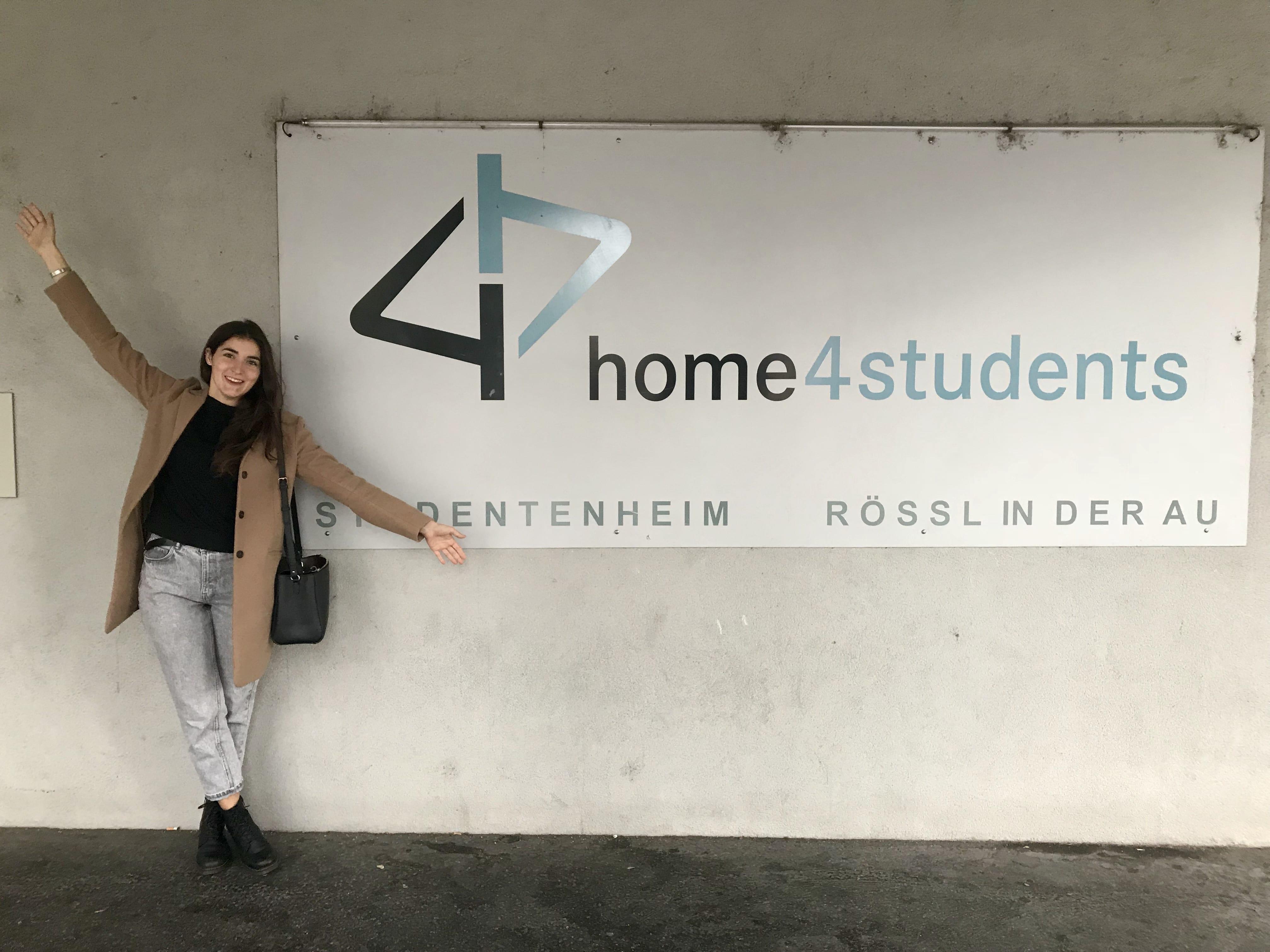 Ambassadorin Sara vor dem home4students Eingangs-Schild