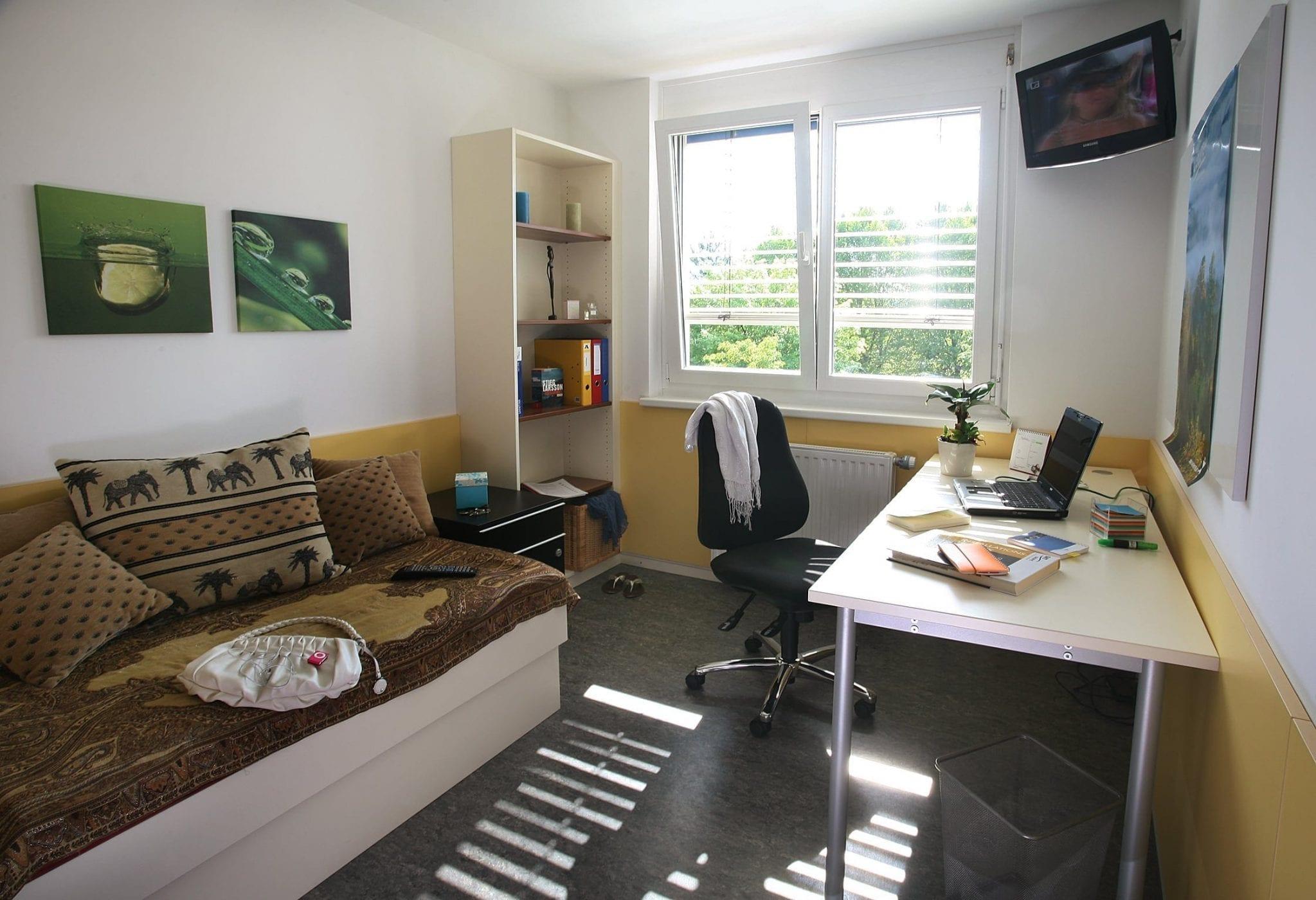 Einzelzimmer mit TV Gerät, Bett, Schreibtisch, Bücherregal
