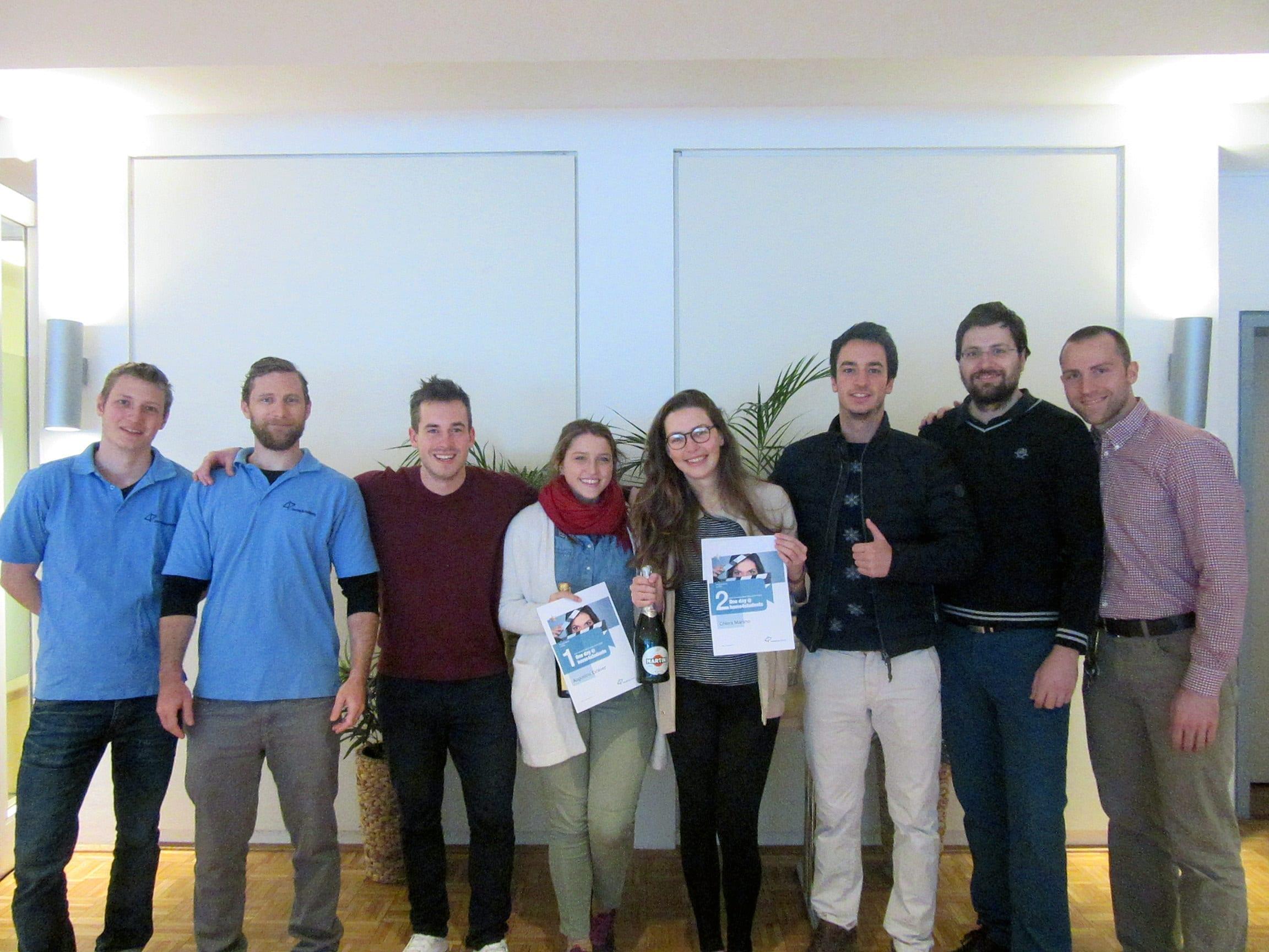Gewinnerin und Mitarbeiter lächeln in die Kamera