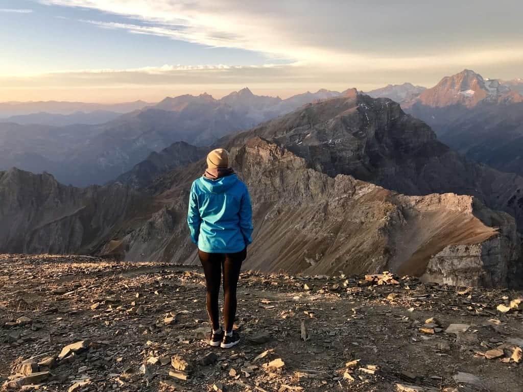 Sara steht vor einer atemberaubenden Berglandschaft