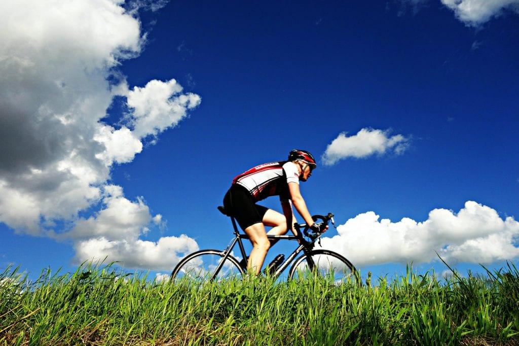 Radfahrer, Wolken und ein blauer Himmel