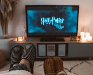 Wohnzimmer, zwei Füße in Hausschuhen, dahinter ein TV mit Harry Potter