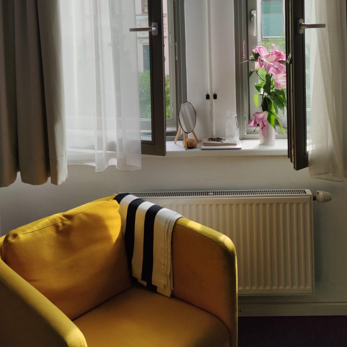 Gelber Sessel, geoeffnets Fenster