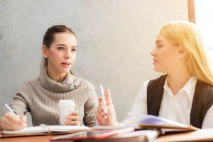 zwei Frauen sitzen mit Notizbüchern an einem Tisch